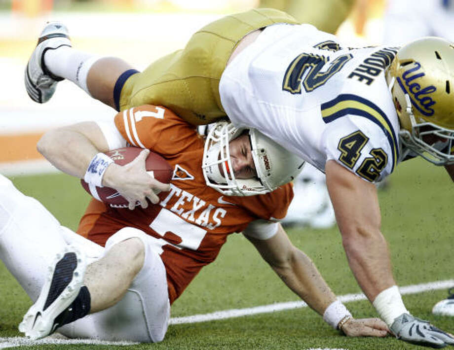 The roughest day of Garrett Gilbert's young career as Texas quarterback included this hit by UCLA's Patrick Larimore and two turnovers in the Longhorns' 34-12 loss. Photo: VERNON BRYANT, Dallas Morning News