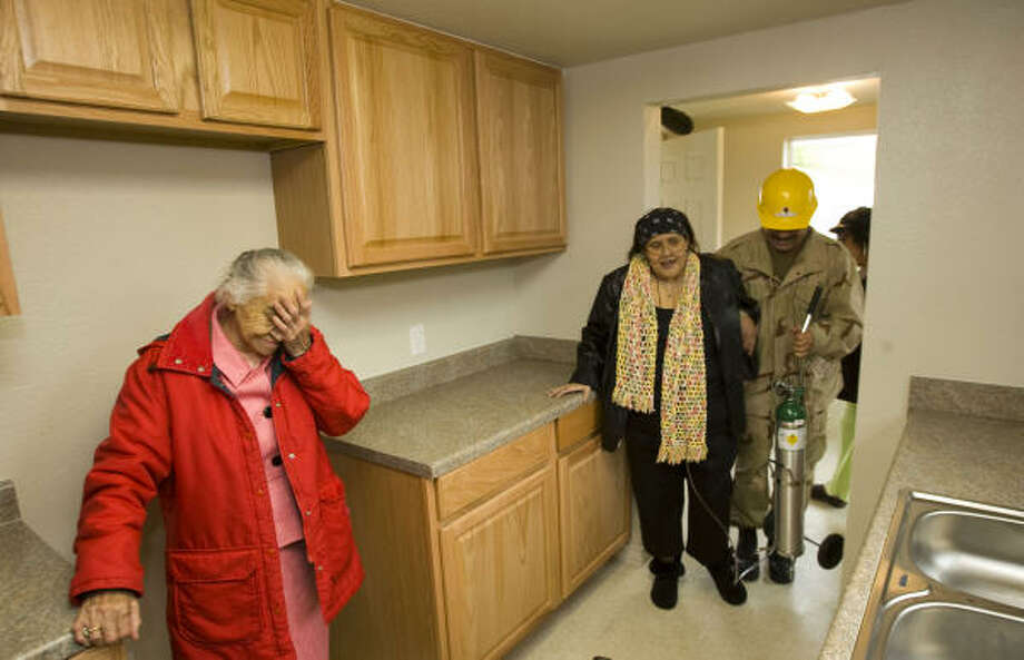 Maria Aguirre, left, reacts as her daughter Maria Huerta walks through her rebuilt home for the first time Tuesday. Photo: Brett Coomer, Chronicle