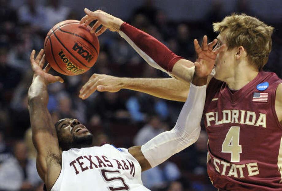 Texas A&M's Dash Harris falls backward after Florida State's Deividas Dulkys blocked his shot. Photo: Jim Prisching, AP