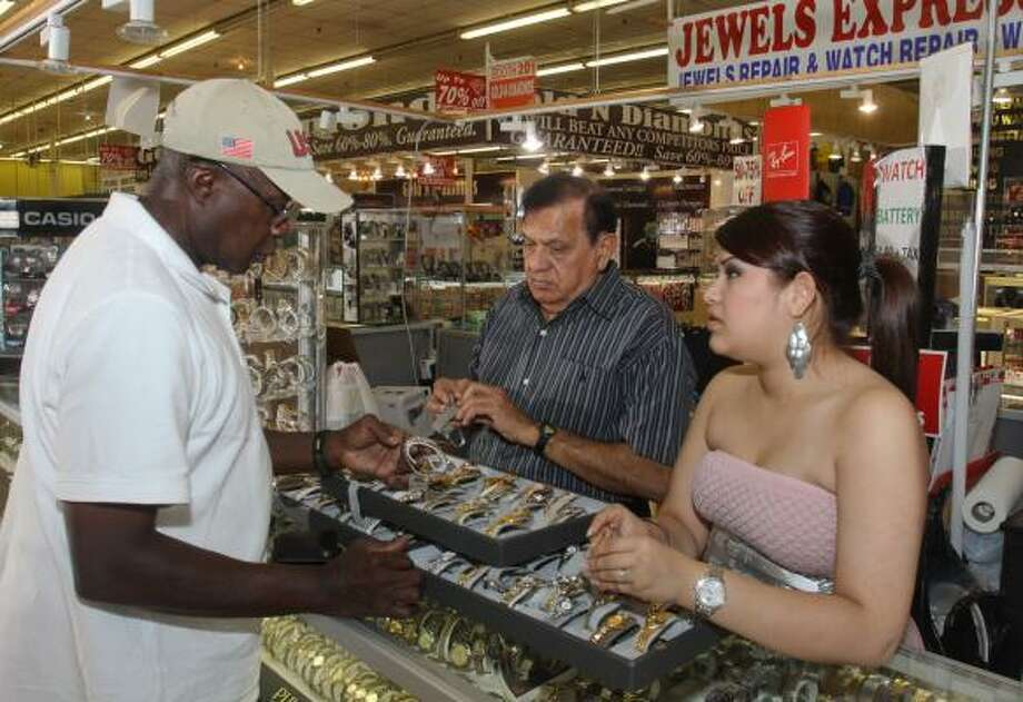 Marshall Valentine, left, shops for a watch for his aunt as Abbasali Sattani and Paloma Estrada help him. Sattani, who has owned his business for 17 years, is among dozens of vendors in The International Common Market of Houston who must move. Photo: Gary Fountain :, For The Chronicle