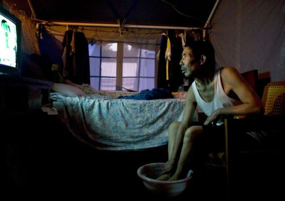 A man in Dujiangyan, China, washes his feet while watching TV in his tent Monday, where he has lived since last month's deadly earthquake. The government is trying to create shelter for 5 million. Photo: PAULA BRONSTEIN, GETTY IMAGES