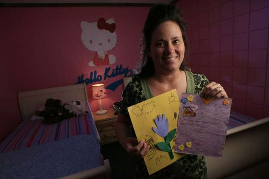 Angie Colbert, of Kidz Harbor, displays art from FLDS children who stayed at the Brazoria County shelter, which housed 24 children. Photo: ERIC KAYNE, CHRONICLE