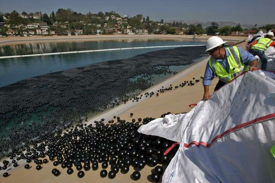 Utility worker Manuel Martinez empties a bale of plastic balls into the Ivanhoe reservoir in Los Angeles on Monday. Photo: Irfan Khan, Associated Press
