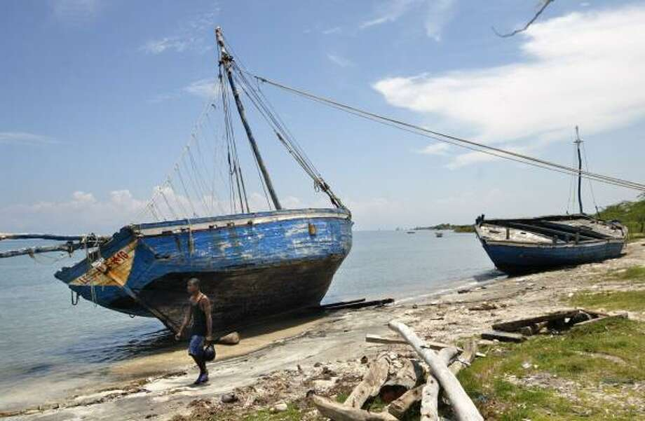 Old rickety boats held together with nothing more than rusty bolts and bent nails rest on the shore in Leogane, Haiti. The vessels may be used again to escape a nation beset by soaring food prices. Photo: LANNIS WATERS, PALM BEACH POST