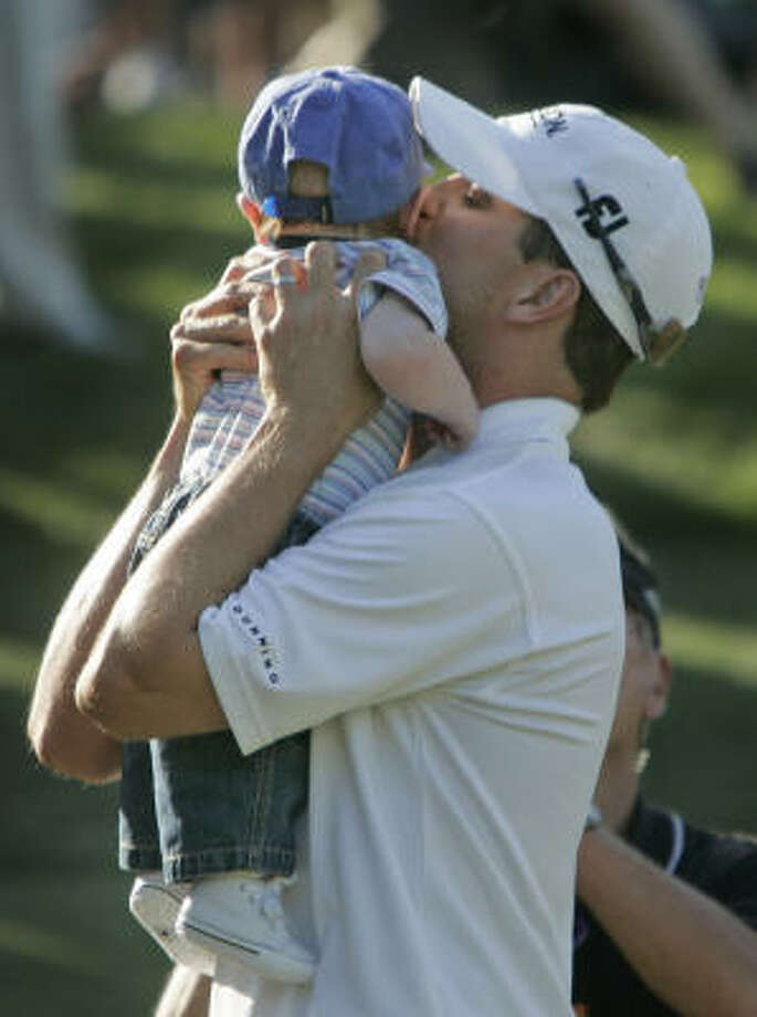 Zach Johnson celebrates with his four-month-old son, Will, after defeating Ryuji Imada in a one-hole playoff to win the AT&T Classic. Photo: John Bazemore, AP