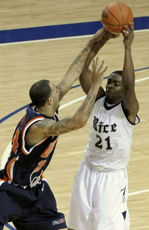 Rice's Rodney Foster tries to pass the ball over Texas-El Paso's Travis Watts during the first half on Wednesday at Tudor Fieldhouse. Photo: Pat Sullivan, AP