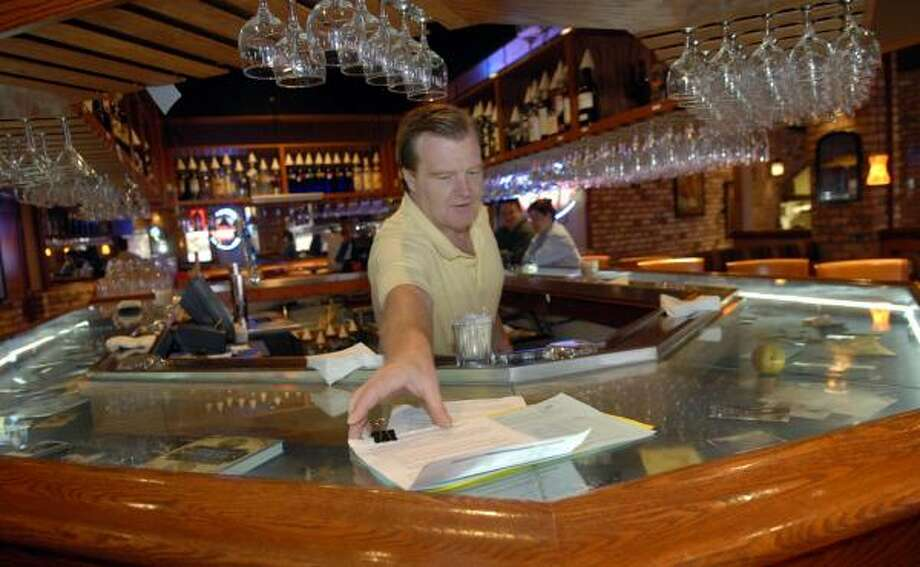 Makenzie's American Grill bartender Jay Theis reaches for a petition on the bar that would allow restaurants to sell alcohol without a membership to a private club in Brazoria County. Photo: KIM CHRISTENSEN, FOR THE CHRONICLE