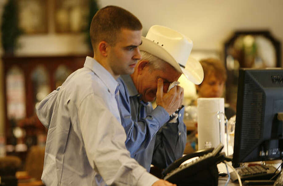 "Gallery Furniture founder Jim ""Mattress Mack"" McIngvale and his son, James, spend an emotional Friday at the business's Post Oak location after Thursday's blaze.  Photo: Julio Cortez, Chronicle"