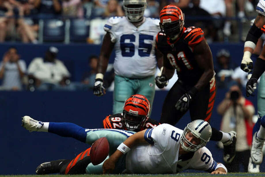 Quarterback Tony Romo #9 of the Dallas Cowboys fumbles the ball against Frostee Rucker #92 of the Cincinnati Bengals. Photo: Ronald Martinez, Getty Images
