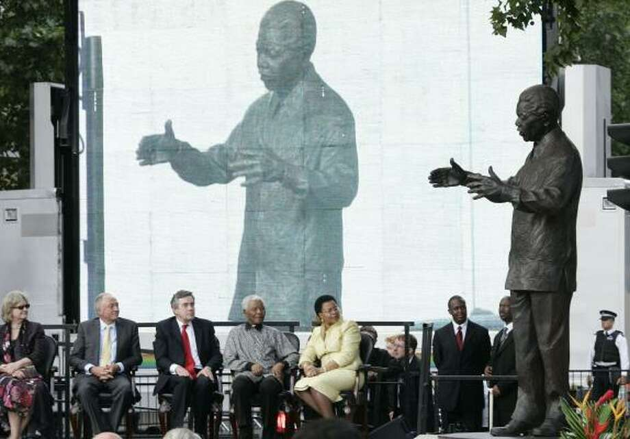 Nelson Mandela, seated second from right, attends the unveiling of his statue in London on Wednesday. Photo: SANG TAN, ASSOCIATED PRESS