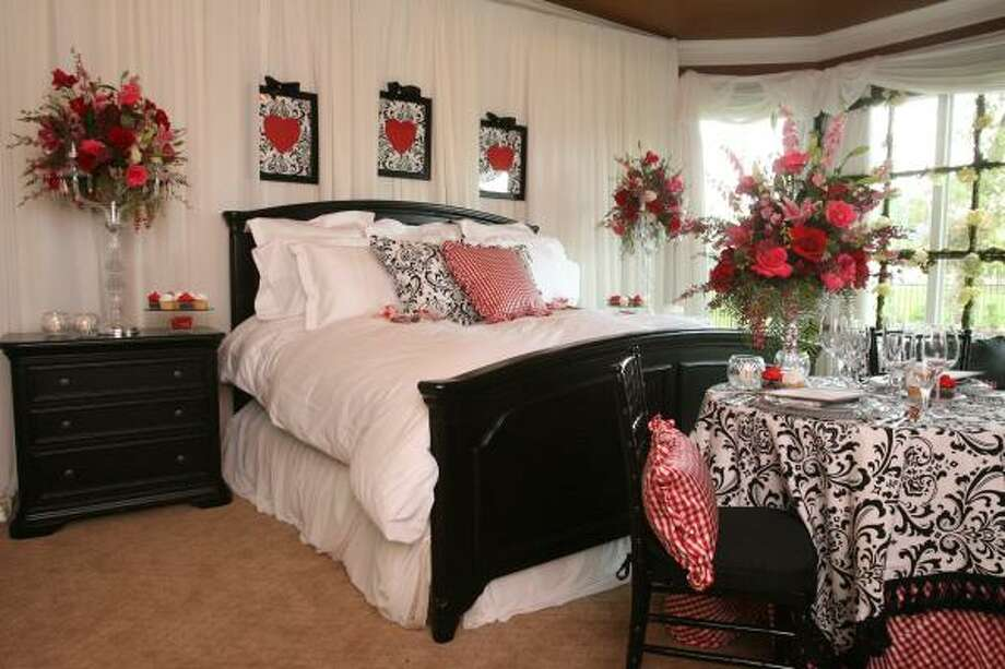 Erika Mannke created a bold Valentine's Day room in black, white and red. A romantic table for two is set at the foot of the bed. Photo: Bill Olive, For The Chronicle