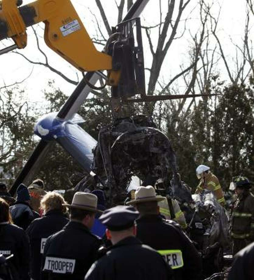 Workers remove debris Monday at the scene of the Continental Connection Flight 3407 crash in Clarence, N.Y. Photo: David Duprey, Associated Press