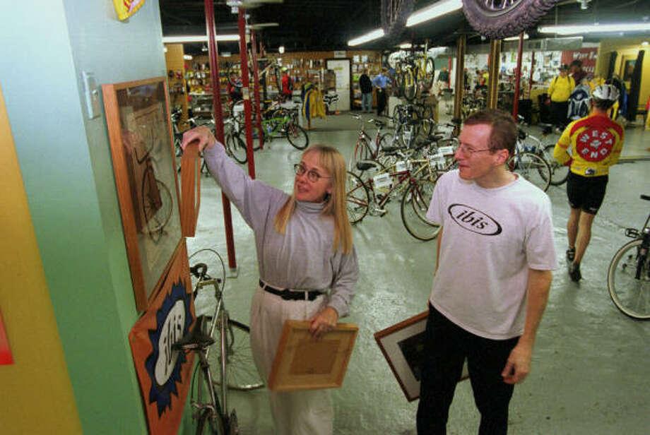 Gallery owner Kathleen Packlick helps her husband, Daniel Murphy, hang art in his bike shop, West End Bicycles. Photo: Ben DeSoto, Houston Chronicle