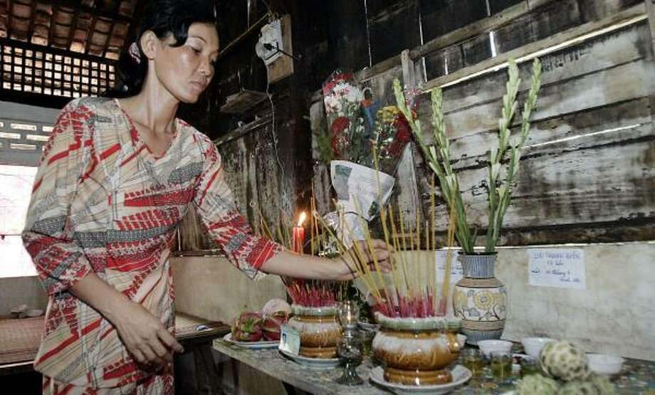 Le Thi Dung, 43, burns incense for her two sons, Luu Tan Dien, 17, and Luu Tan Mai, 19, who were killed in the collapse of a bridge under construction. Her husband and another son were injured. Photo: TRAN VAN MINH, ASSOCIATED PRESS