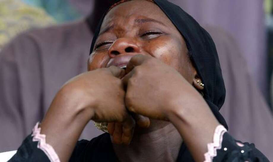 The wife of a dead Nigerian soldier killed in Darfur weeps during her husband's burial in Abuja, Nigeria, on Friday. Photo: PIUS UTOMI EKPEI, AFP/GETTY IMAGES