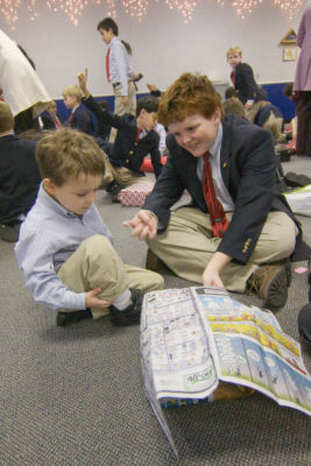 TEAM WORK: J.W. Johnson, 4, and Nicholas Espenan, 14, team up on a box at the Regis School?s annual wrapping party last month. The event was part of the school?s extracurricular programs  created to teach the students about social tolerance. Photo: R. Clayton McKee, For The Chronicle