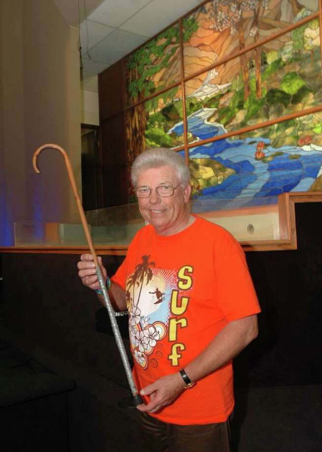 John Morgan, founder of Sagemont Church hold the old cane belong to a former member, Hiram Woosley, who died in November 2010. The old cane auction price is currentlt at $68,000. Photo: George Wong / Freelance