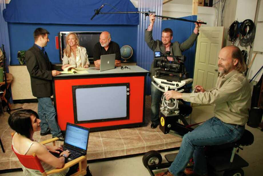 The MetroWeb TV crew members produce a variety of programming, including newscasts, entertainment series and reality shows. From Left, Nickie Brown manages the technical aspects of the scene and Victor San Miguel discusses dialogue with Kimber Ray Sadler and Al Hayter. Tyler Forner, operations manager, positions the mic, while Gary Parker, president and videographer, prepares to capture it all on film.