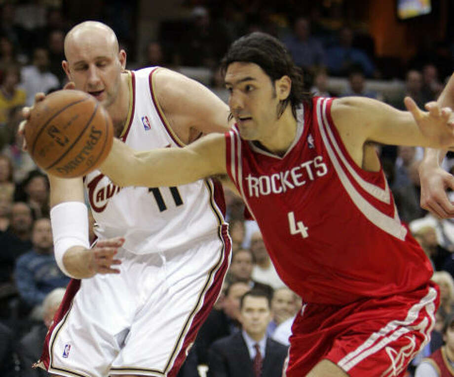 Luis Scola of the Rockets grabs a loose ball in front of the Cavs' Zydrunas Ilgauskas on Tuesday. Photo: Mark Duncan, AP