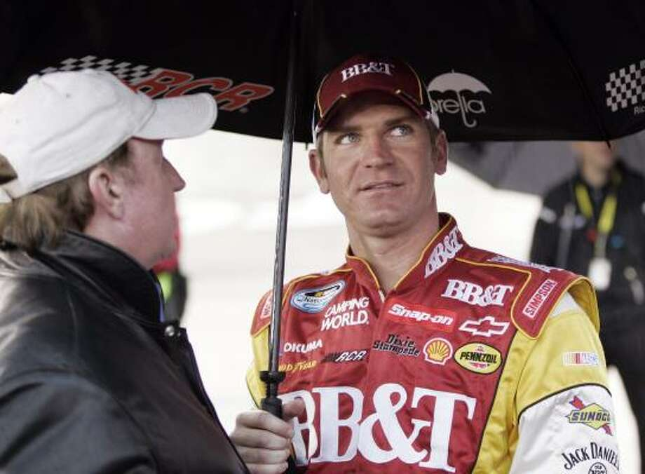 Clint Bowyer, right, talks with team owner Richard Childress while they wait under an umbrella during a rain delay in the Sharpie Mini 300 at Bristol Motor Speedway. Bowyer won the rain-shortened race after 171 laps. Photo: Wade Payne, AP