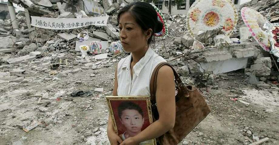 Feng Jun, mother of a victim who died in the collapse of a school during the May 12 earthquake, walks at the site in Juyuan, China. Photo: EUGENE HOSHIKO, ASSOCIATED PRESS
