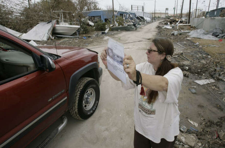 Kat Joel-Reich, 56, right, holds up a sign with the photos and information of Biscuits and Toonees, two cats owned by her friend Jennie Gounah that went missing after Gounah's house collapsed during Hurricane Ike, as she asks people in a car if she's seen the cats roaming anywhere in Galveston Island. Photo: Julio Cortez, Chronicle