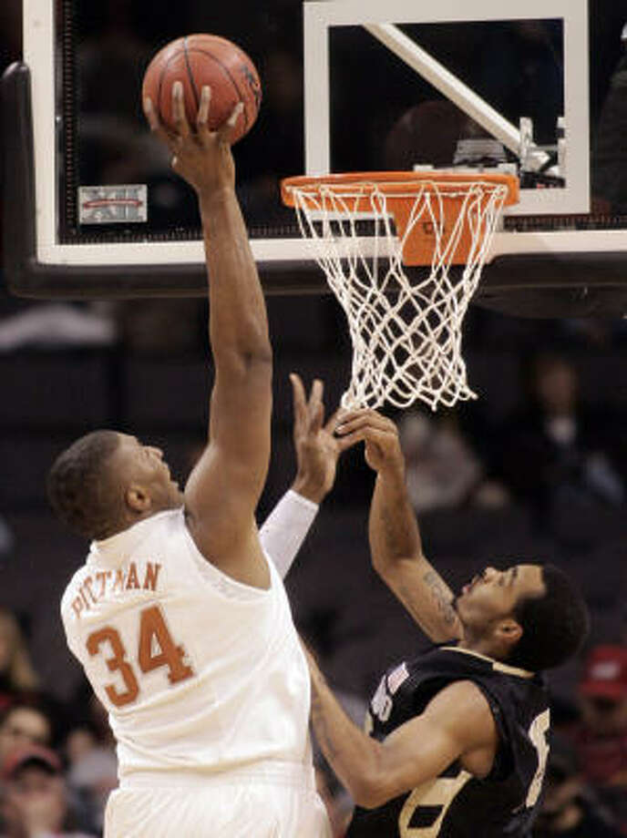 Texas' Dexter Pittman reaches to dunk over Colorado's Toby Veal on Wednesday during the first round of the Big 12 men's tournament. Photo: Sue Ogrocki, AP