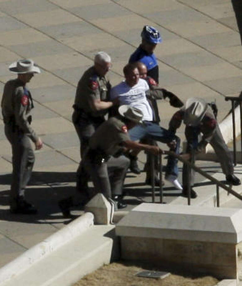 State troopers take a man into custody moments after reports of gunfire Thursday on the steps of the Texas Capitol. A DPS spokeswoman said nobody was wounded. Photo: Vida  Walker Burtis, Associated Press