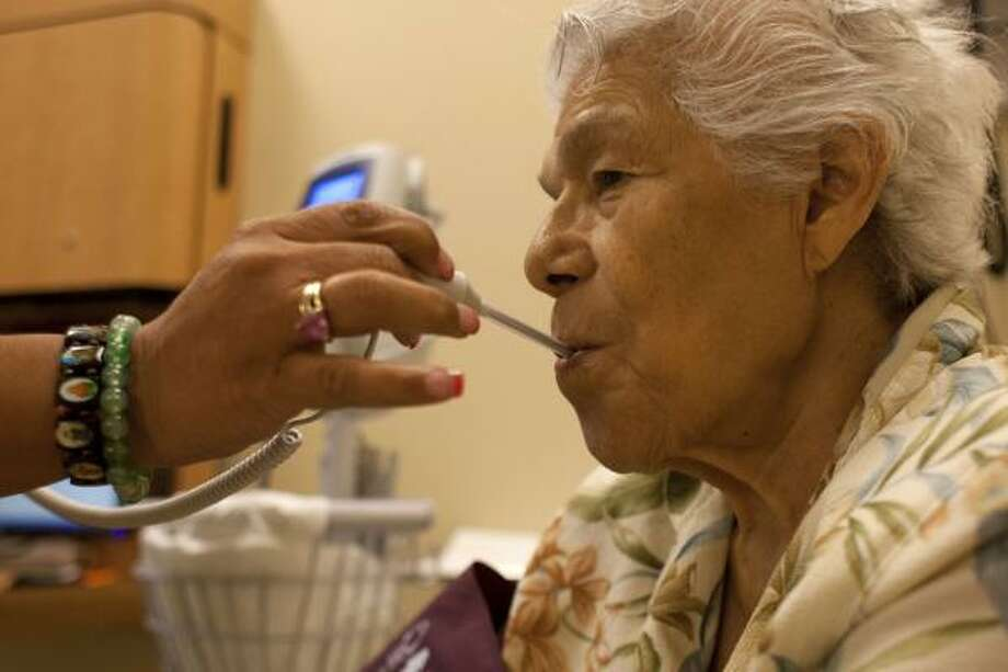 Isabel Nuñez, 86, gets her temperature taken at the UT Center for Healthy Aging. In her recent visit there, an examination by a geriatric primary care physician revealed that Nuñez might be showing early signs of dementia. Photo: Johnny Hanson, Houston Chronicle
