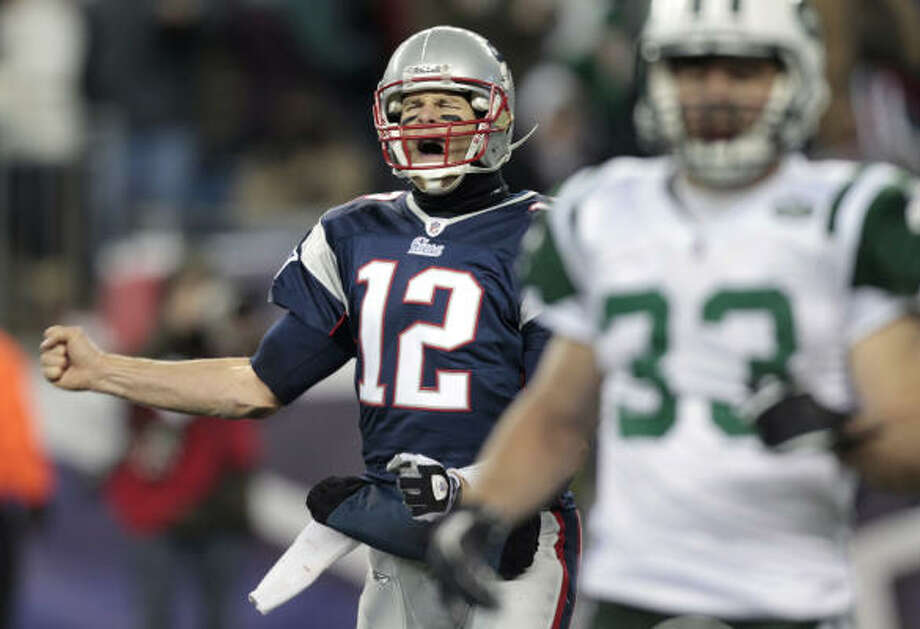 New England Patriots quarterback Tom Brady, left, celebrates a touchdown by teammate Aaron Hernandez against the New York Jets during the second half on Monday night. Photo: Charles Krupa, AP