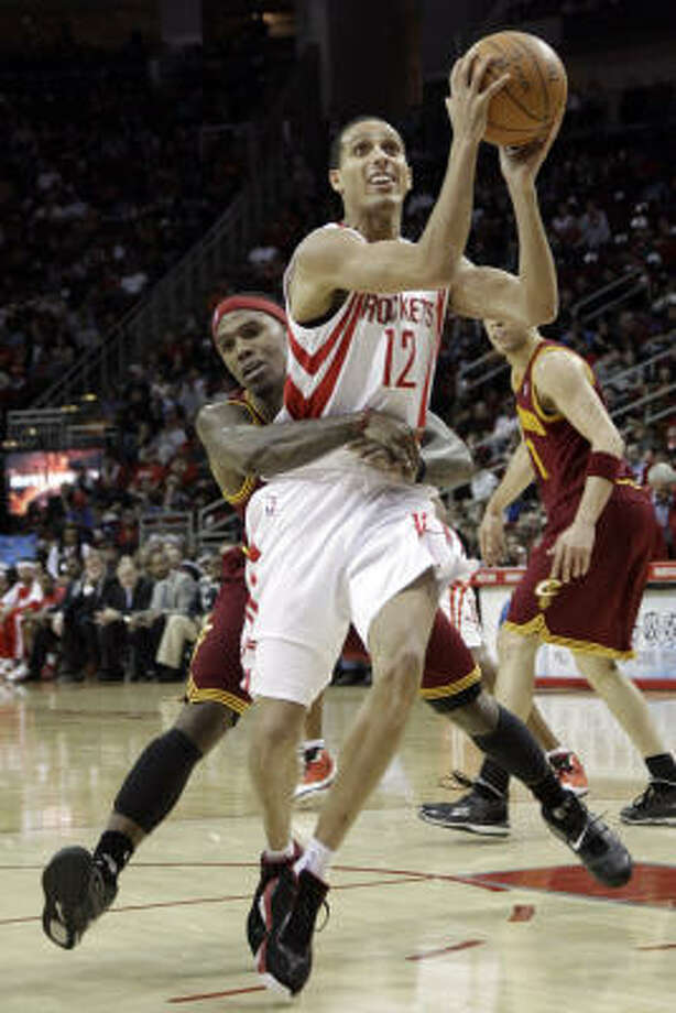 Rockets guard Kevin Martin (12) is fouled from behind by Cleveland Cavaliers guard Daniel Gibson during Saturday night's victory. Photo: David J. Phillip, AP