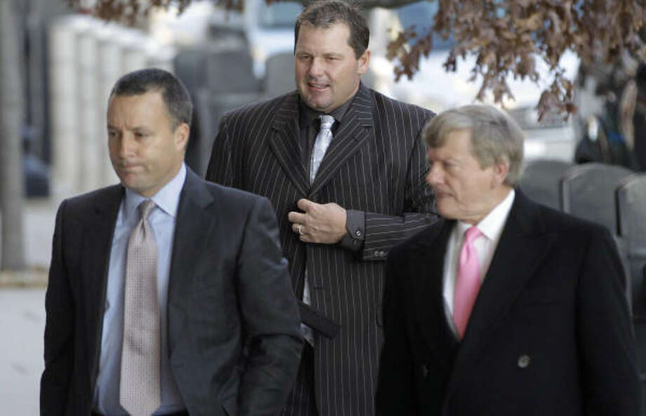 Former Cy Young Award winner Roger Clemens, center, is being represented by lawyers, Michael Attanasio, left, and Rusty Hardin. Photo: Charles Dharapak, AP