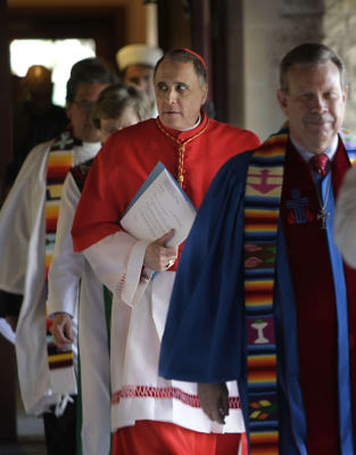 Cardinal Daniel DiNardo, carrying papers, was among the local religious leaders attending an interfaith prayer service to renew a call for immigration reform.