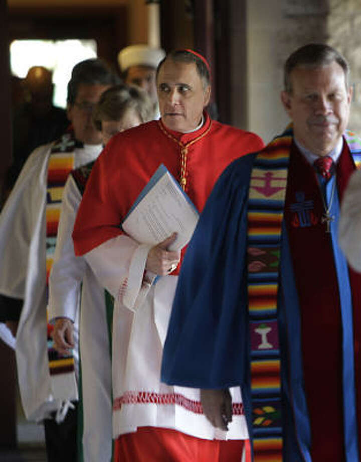 Cardinal Daniel DiNardo, carrying papers, was among the local religious leaders attending an interfaith prayer service to renew a call for immigration reform. Photo: Mayra Beltran, Chronicle