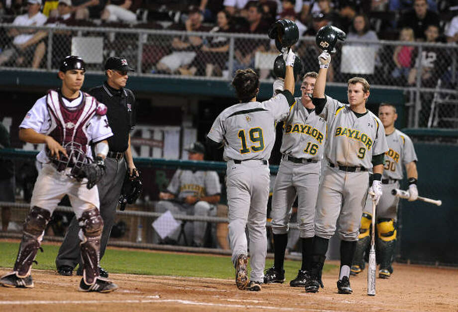 Baylor's Logan Vick (19) is welcomed home by teammate Brooks Pinckard (16) and Max Muncy (9) after his two-run homer off of A&M relief pitcher Brandon Parrent in eighth inning on Saturday. Photo: Rod Aydelotte, AP