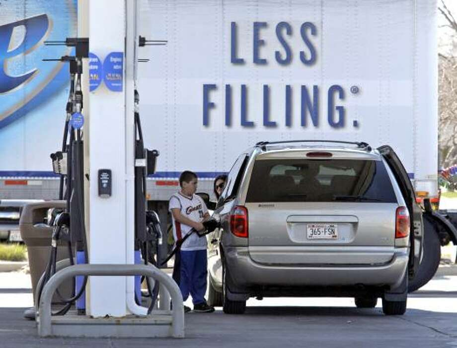 A beer slogan on a truck doesn't seem appropriate at a gas station Wednesday in Sheboygan, Wis. Gasoline hit a national average of $3.982 per gallon. Photo: Bruce Halmo:, Associated Press