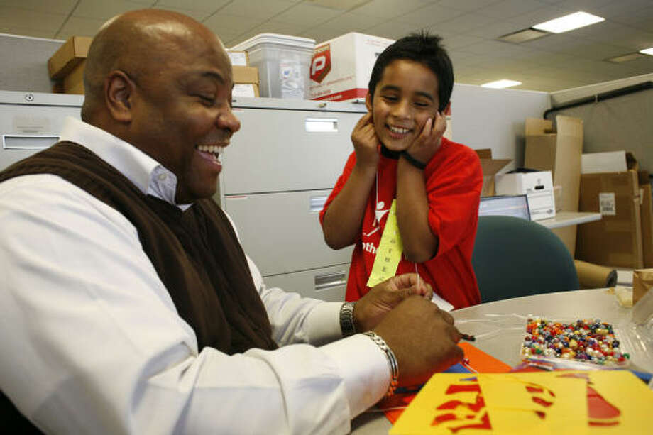 Billy Wright struggles with small beads as he and Juan Cid, 8, create Thanksgiving necklaces at Comcast's Houston headquarters recently. Photo: Eric Kayne, For The Chronicle