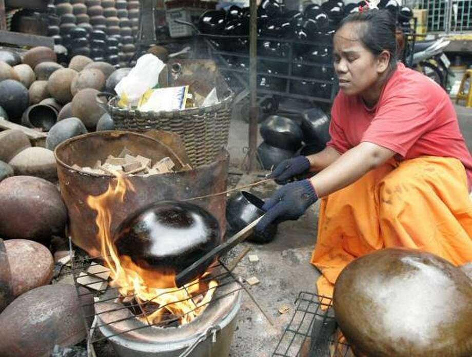 A Thai woman burns a Buddhist alms bowl on a stove in the Rattanakosin community in Bangkok. The community of traditional Buddhist alms bowl makers is shrinking because most monks in Thailand now buy factory-made goods. Photo: APICHART WEERAWONG, ASSOCIATED PRESS