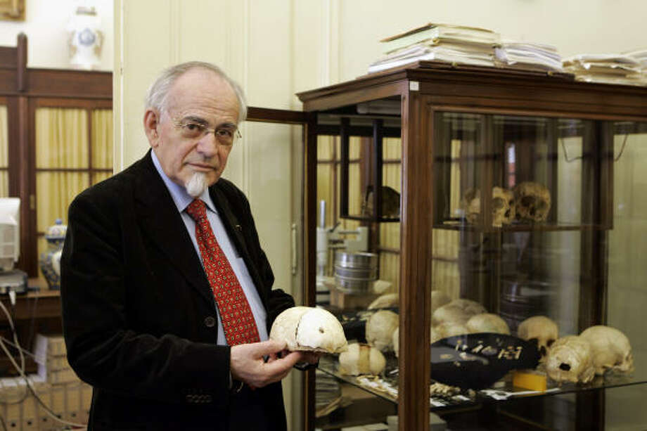 Miguel Telles Antunes, curator of Lisbon's Academy of Sciences Museum, holds the skull of a 3-year-old child. Experts say the skull and countless human remains found in a mass grave in Portugal were victims of an earthquake that devastated Lisbon in 1755. Photo: ARMANDO FRANCA, AP