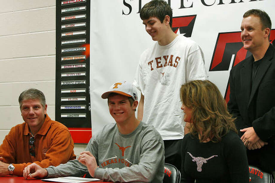 Garrett Gilbert, seated center, quarterback for Lake Travis High School, sits between his father, Gale, left, and mother, Kim, right, while brother Griffin and coach Chad Morris, right, stand behind him on Wednesday at the high school in Austin. Gilbert signed a letter of intent to play football at the University of Texas. Photo: Rodolfo Gonzalez, AP