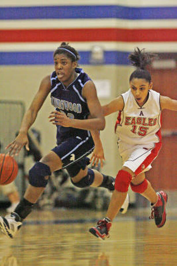 Kingwood's Michelle Price, left, drives down the lane with Atascocita's Rachel Arthur in pursuit on Tuesday night. Photo: Eric Kayne, Chronicle
