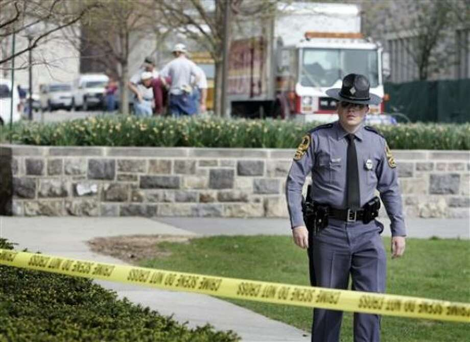 A Virginia State Police officer patrols the Virginia Tech campus Wednesday as workers build a fence around Norris Hall in Blacksburg, Va. Norris Hall was the scene of a shooting rampage where gunman Seung-Hui Cho killed 30 people before committing suicide. Photo: Evan Vucci, AP