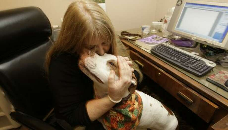 Attorney Zandra Anderson embraces her dog Zeus at her home office. Anderson decided to combine her career as a lawyer and her love of dogs. Photo: BRETT COOMER, CHRONICLE