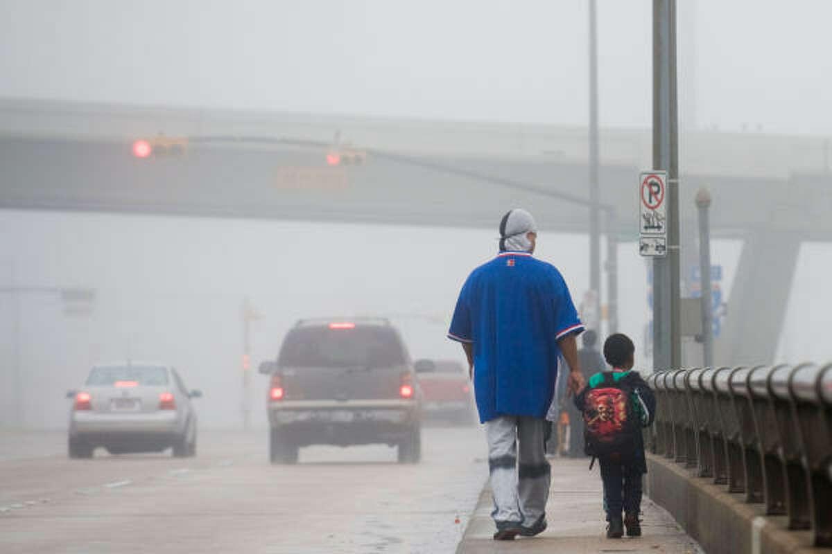 Dense fog shrouds pedestrians crossing the Taylor Street bridge over I-10 on Thursday, Dec. 18, 2008, in Houston.