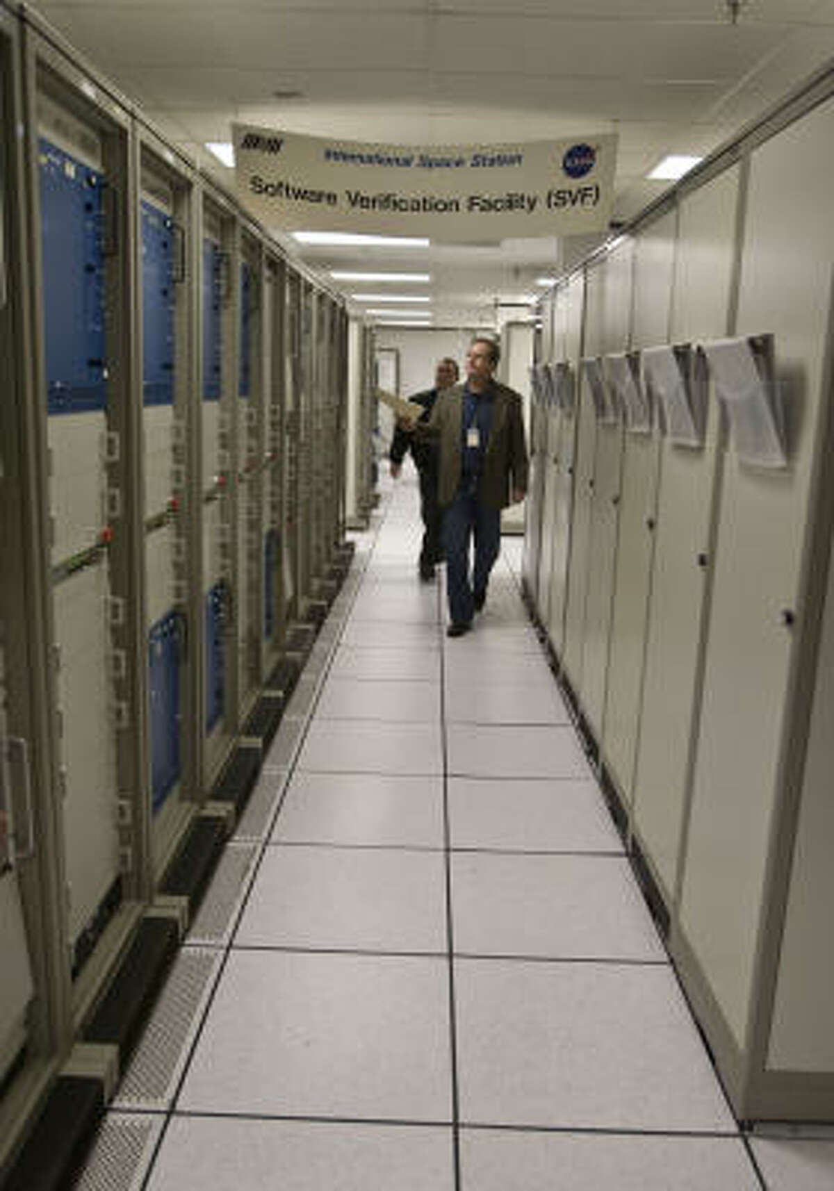 Boeing's Cary Cheatam, left, and Steven Cox walk along a bank of computers at the software verification facility where computers used on the International Space Station are tested. The station will get new core programming in 2011.