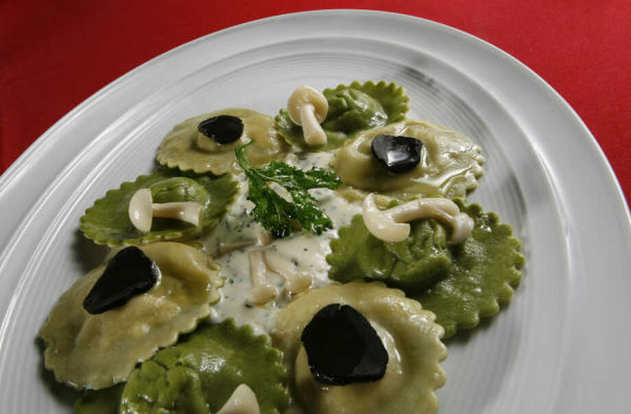 The asparagus ravioli features a lush, satiny filling inside and includes a butter sauce with thin shards of black truffle on top. Photo: Julio Cortez :, Chronicle