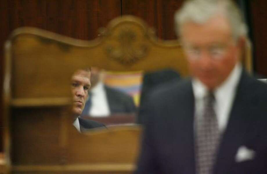 Defendant David Temple is seen in the mirror of a wooden hutch as his attorney Dick DeGuerin walks by during his trial Tuesday. Prosecutors brought in the hutch from Temple's home in an attempt to refute his testimony on what happened the day of his wife's slaying. Photo: STEVE UECKERT, CHRONICLE