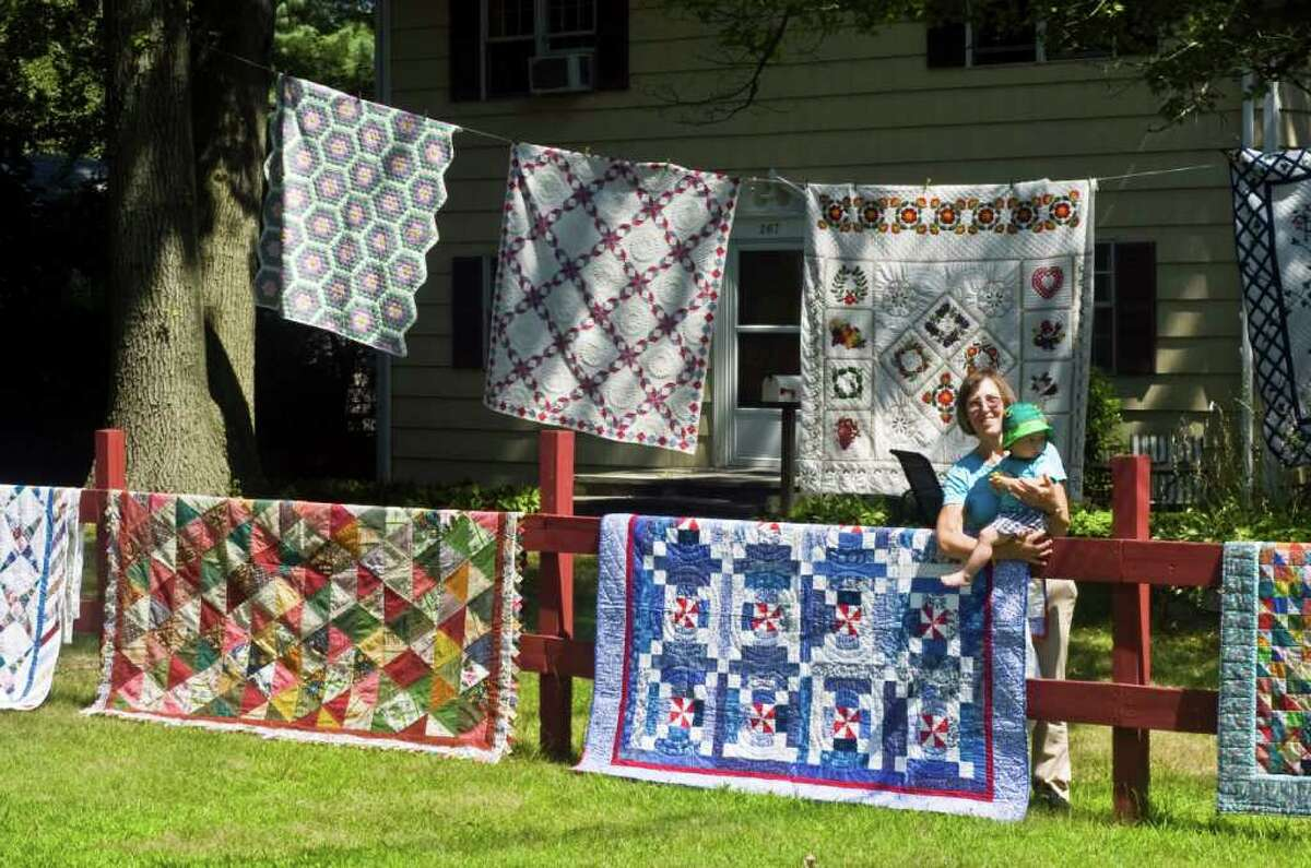 Sonhild Rodney and her grandson Martin Bailey showoff her quilting handiwork by displaying more than 25 quilts on her lawn and in trees around her Loveland Road home in Stamford, Conn., July 26, 2011. Rodney has been quilting for more than 25 years and has made 87 quilts.