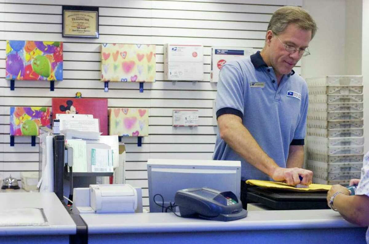 Martin Schoenfeld handles a package in the Glenbrook Post Office in Stamford, Conn., July 26, 2011. The United States Postal Service is considering closing the Glenbrook Post Office.
