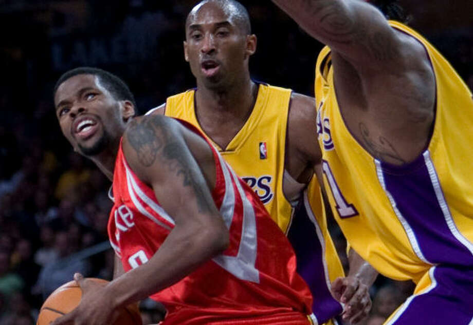L.A.'s Josh Powell, right, and Kobe Bryant make life difficult for Aaron Brooks while navigating the lane in the first half. Photo: Nick De La Torre, Chronicle